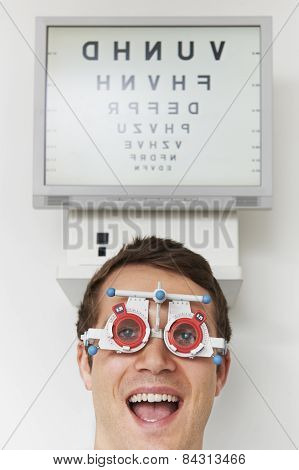 Happy Man At Optometrist Having Sight Test