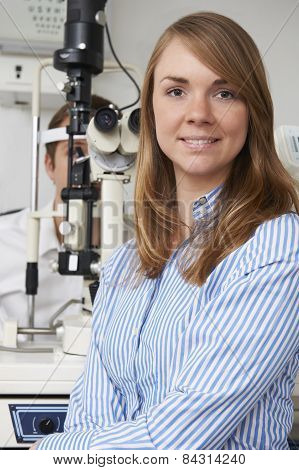 Female Optician Giving Male Client Eye Examination