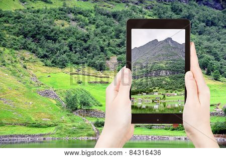 Tourist Taking Photo Of Village In Norway