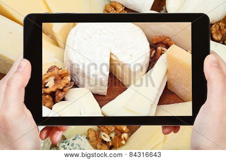 Tourist Taking Photo Of Assortment Of Cheeses