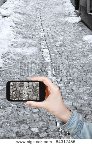 Tourist Taking Photo Of Snowy Cobblestone Road