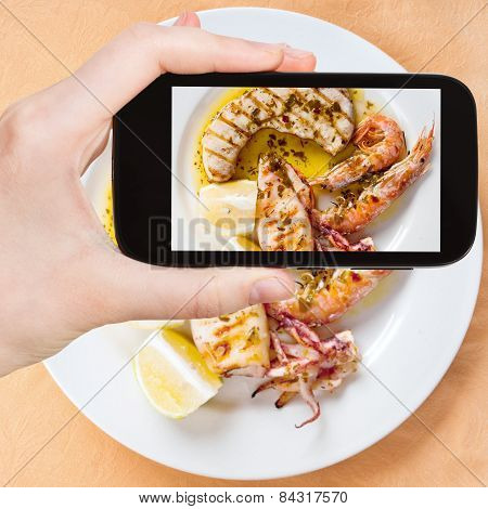 Tourist Taking Photo Of Sicilian Grilled Fish Mix