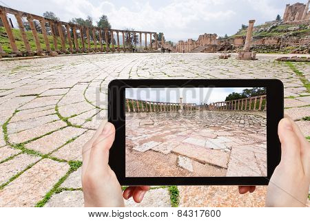 Tourist Taking Photo Of Roman Oval Forum In Jerash