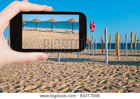 Tourist Taking Photo Of Straw Beach Umbrellas