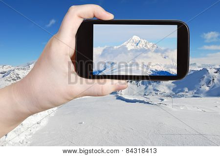 Tourist Taking Photo Of Mountain Peak In Alpes