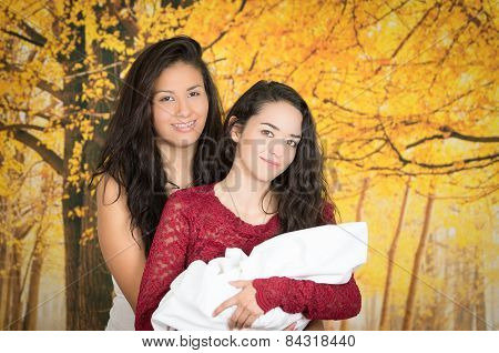 portrait of beautiful lesbian couple holding their baby