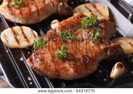 Two Pork Steak Grilled With Onions And Garlic In A Pan Grill