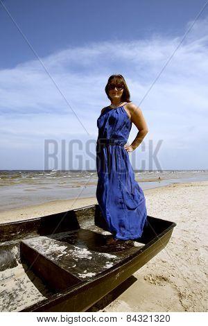 Cute miniature brunette stands in a boat