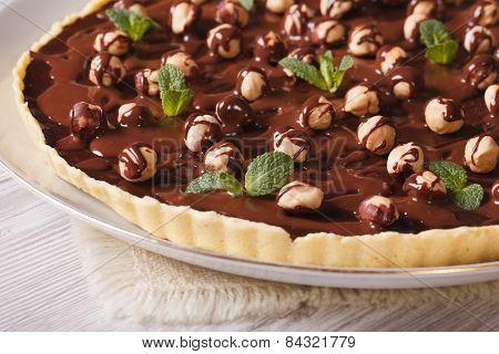 Chocolate Tart With Hazelnut And Mint Close-up. Horizontal