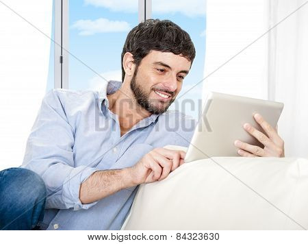 Young Attractive Hispanic Man At Home Sitting On White Couch Using Digital Tablet