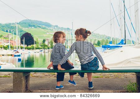 Two kids, little girl and boy resting by the lake, wearing frocks and blue shoes