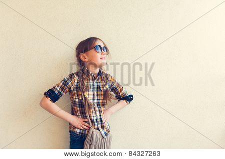 Portrait of a cute little girl wearing yellow and blue plaid shirt and sun glasses