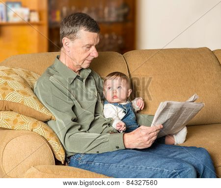 Young Baby Looking Up At Grandad With Paper