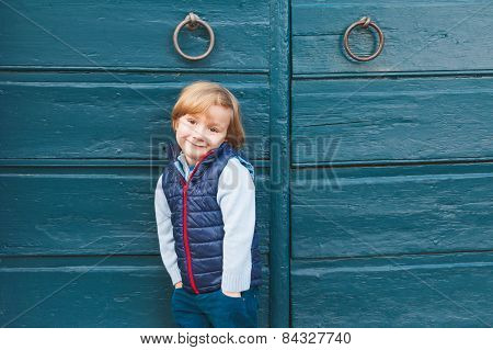 Outdoor portrait of a cute little boy wearing blue waistcoat, standing next to blue wooden door