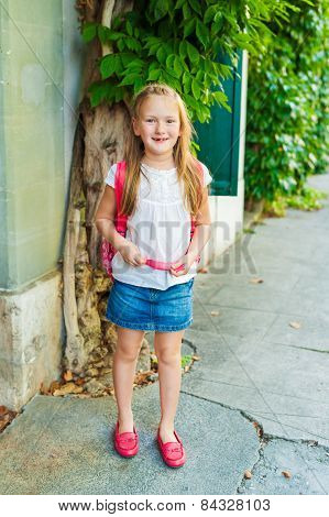 Adorable little girl walking on the street, wearing bright red shoes and backpack