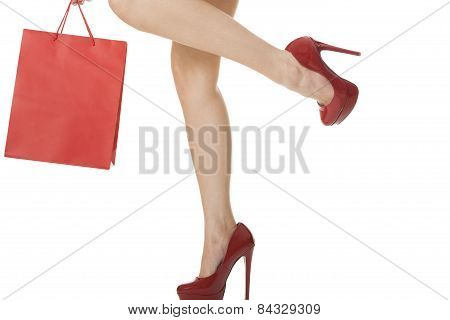 Woman Legs In Red High Heels Carrying Red Bag