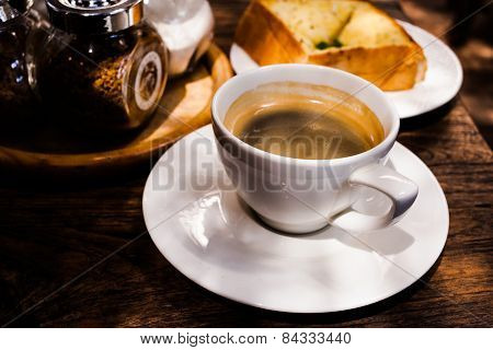 black americano coffee and garlic bread on the table.