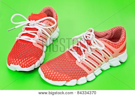 New Orange And White Running Shoes, Sneakers Or Trainers On Green Background