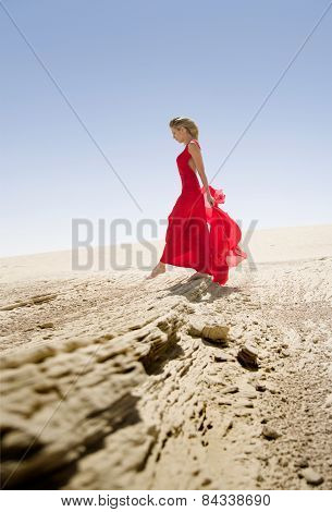 Red dressed beautiful slim woman, walks in desert