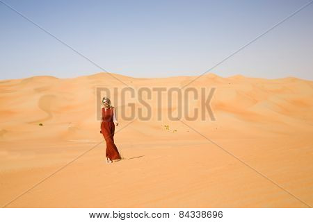 Long dressed woman walks in desert