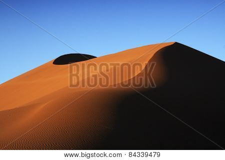 Contours of the rolling dunes of Sossusvlei in the morning light.