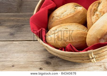 Bread Rolls In A Basket Whith Red Napkin On Old Wood