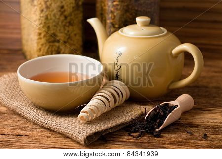 Tea Set On Wooden Board And Spoon With Dry Tea Leafs