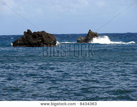 waves breaking against rock