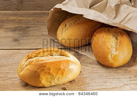 Bread Rolls In A Paper Bag On A Rustic Wooden Table