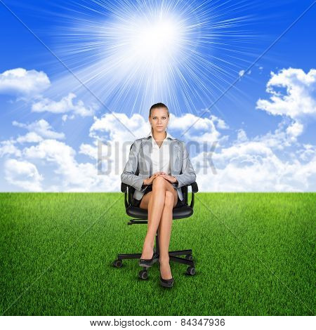 Woman in jacket sits on chair. Background of grass, clouds, sun