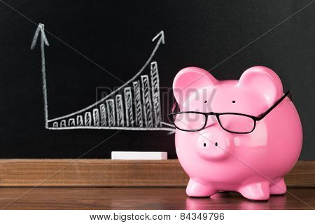 Pink Piggybank With Glasses On Desk