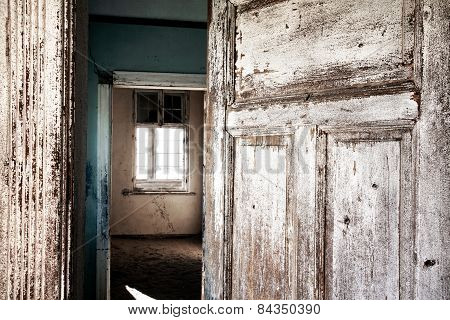 Open door to an abandon room in Kolmanskopp diamond mining town