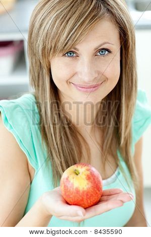 Portrait Of A Beautiful Woman Holding An Apple Looking At The Camera
