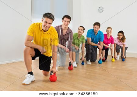 Mature Fitness Instructor With People Exercising