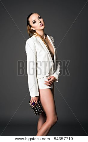 Studio Fashion Shot: Beautiful Girl In White Jacket With Clutch In Hand