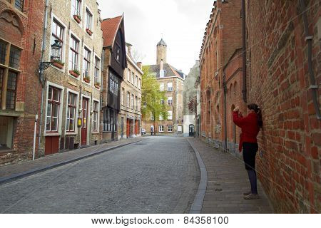 tourist woman taking photo of city Bruges on mobile gadget, Belgium