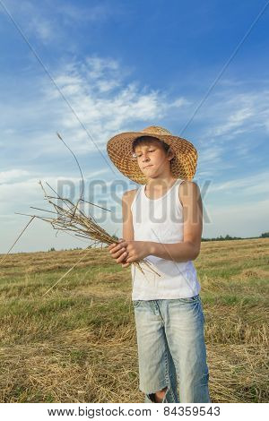 Teenage Farmer Holds Bundle Of Straw