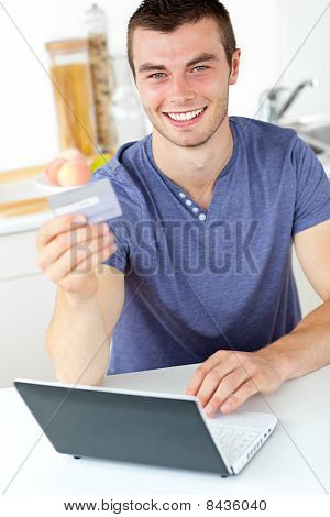 Charismatic Young Man Holding A Card Using His Laptop In The Kitchen