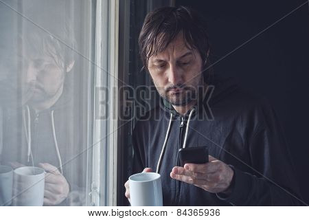 Drinking Coffee And Reading Sms On Mobile Phone In Morning
