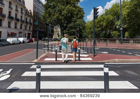 Two People Crossing A Zebra Crossing