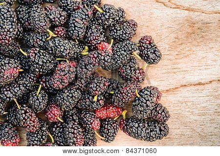 Group Of Mulberries Isolated On Wood Background.