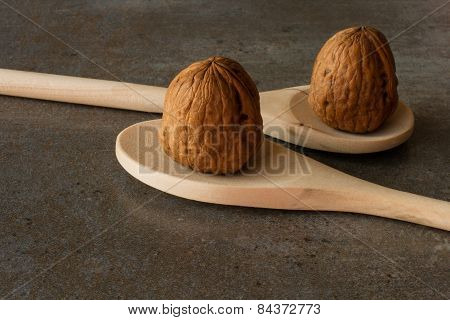 wooden spoon with walnuts on a gray background