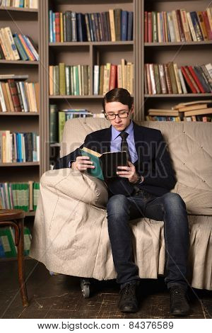 Young Man Is Sitting In A Library And Reading A Book