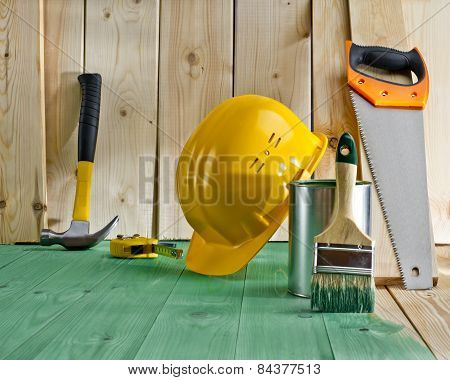 Green Wood Floor With A Brush, Paint, Saw And Yellow Helmet