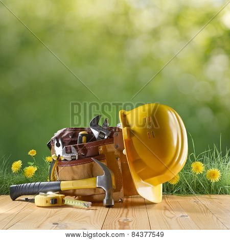 Construction Tool And Helmet On Green Nature Background