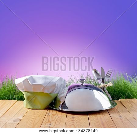 Restaurant Cloche And Chef's Hat On A Background Of Nature