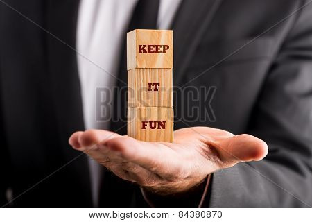 Businessman Holding Three Wooden Cubes Vertically Aligned, With  Keep It Fun Sign