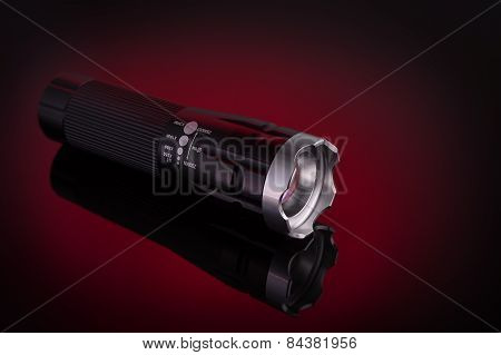 Flashlight With Led Light. On A Red Background.