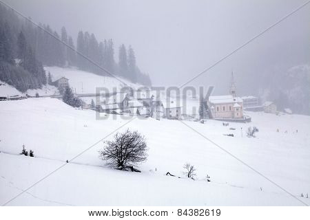 Snowstorm Over Mountains And Alpin Village In Winter, Alps, Switzerland