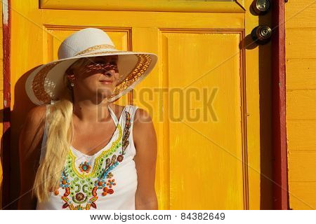 Girl Sitting Near Yellow Beach Hut
